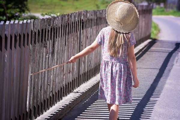 Summer girl in hat with fence